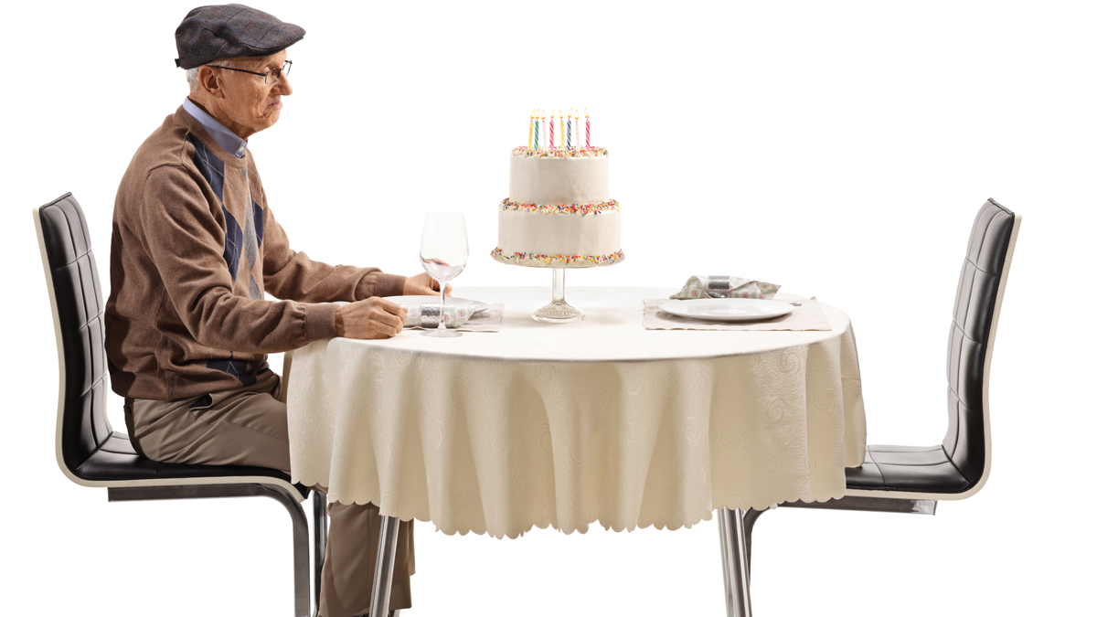 An elderly man sitting alone at a table.