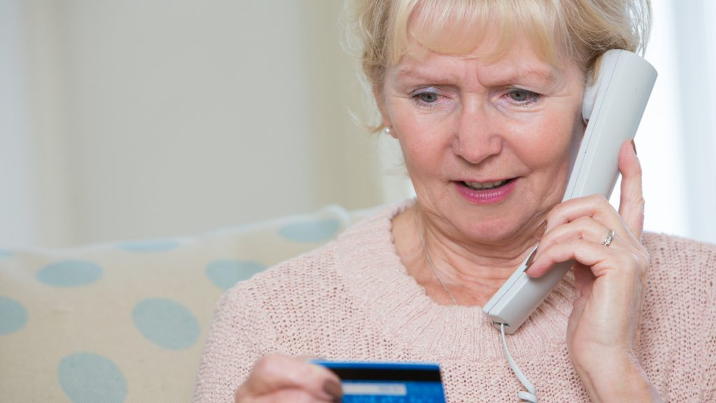 An older woman being scammed by phone.