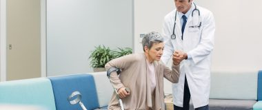 An older woman gets assistance standing from a doctor