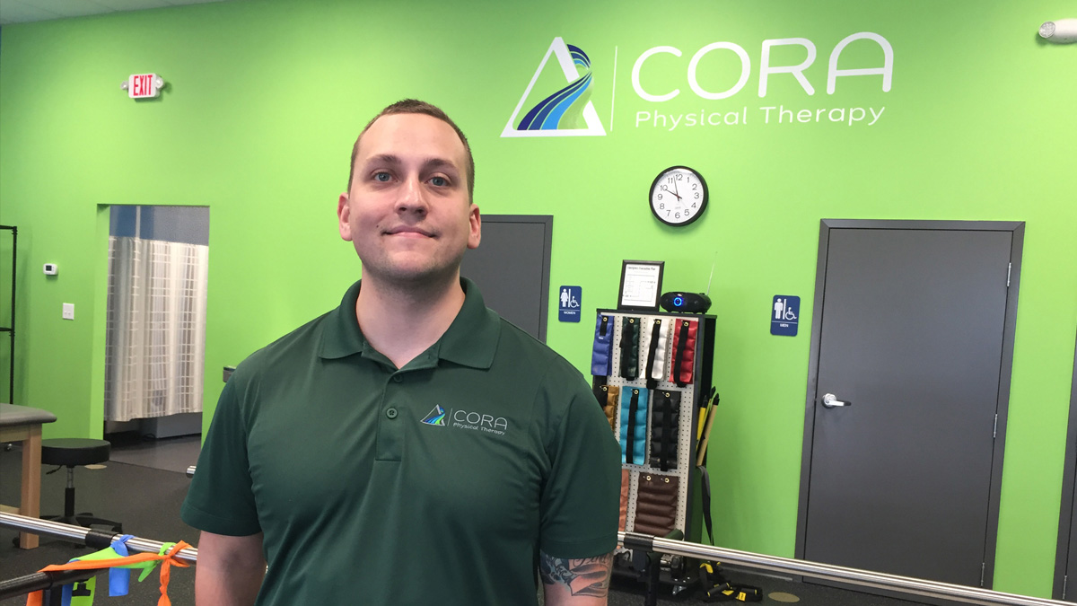 Employee standing in Cora Physical Therapy Facility