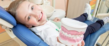 Girl sitting in dental chair holding fake teeth