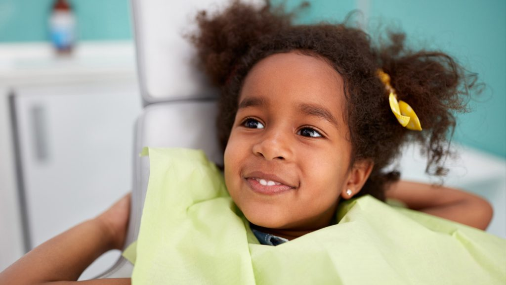 Young girl sitting in dental chair smiling