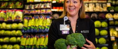 Kerri Stewart the grocery store holding broccoli