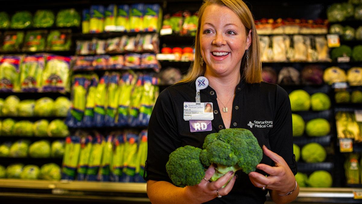 Kerri Stewart the grocery store holding broccoli