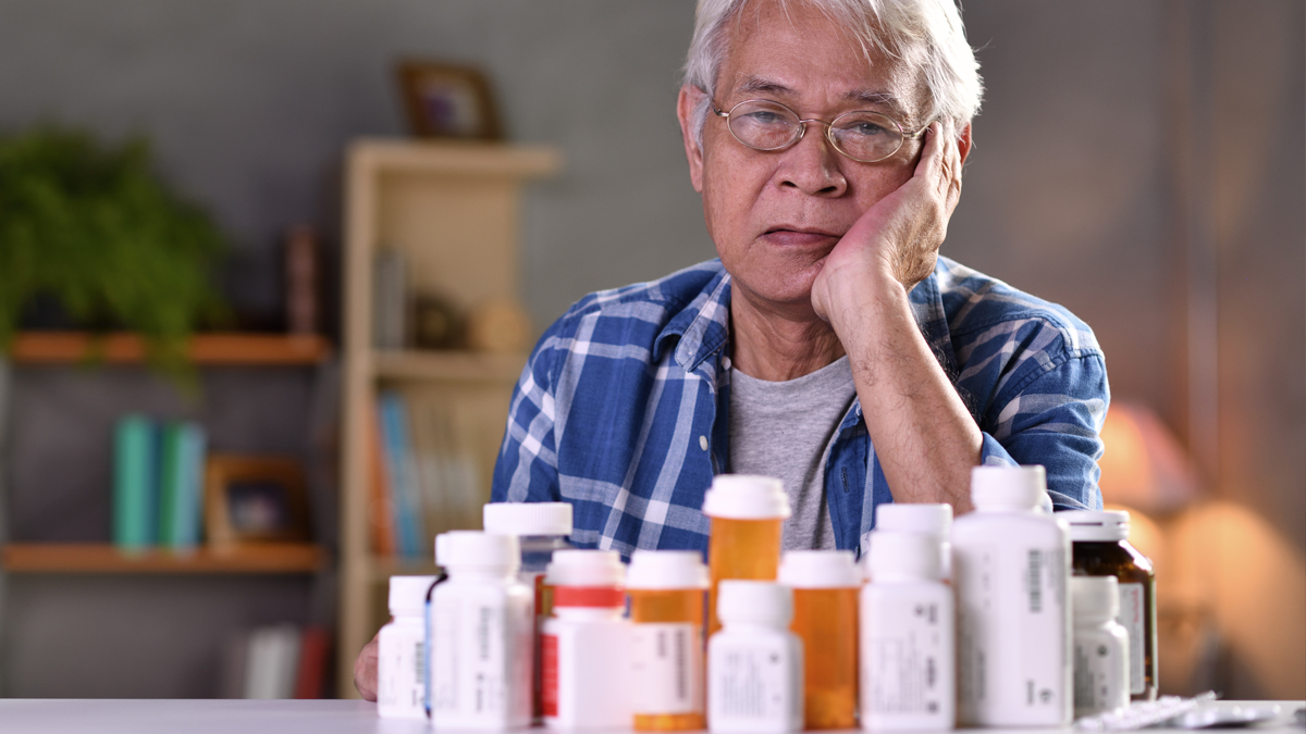 Senior dealing with too many medicine bottles