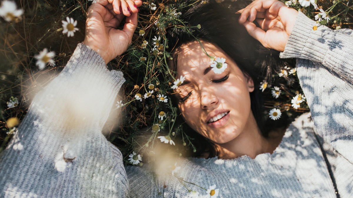 Woman laying on field of grass and flowers dealing with allergies
