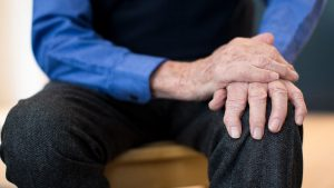 An elderly man with his hands on his knee