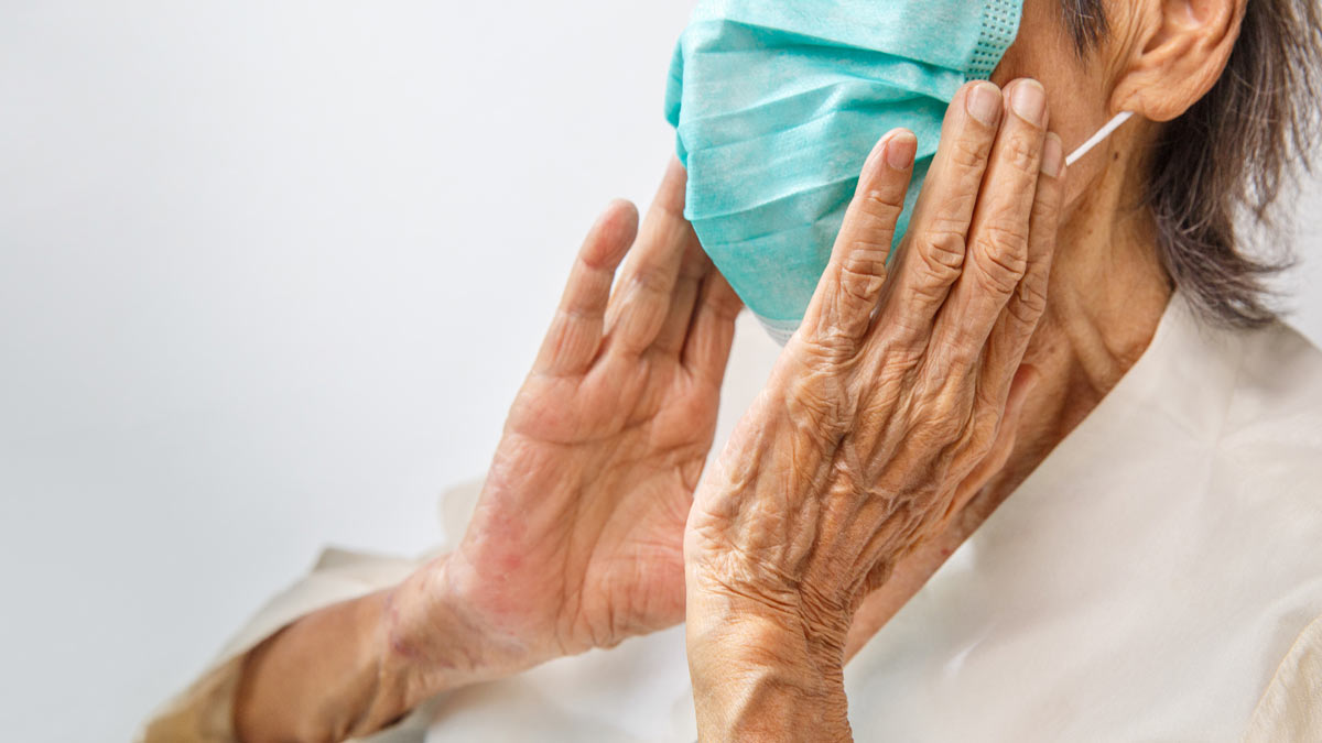An elderly woman adjust a protective face mask.
