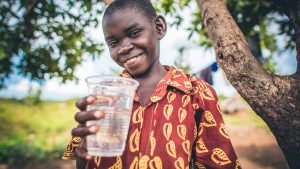 Boy holding cup of water