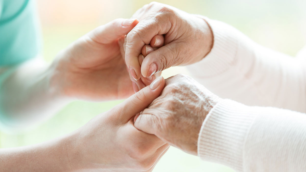 Staff at Pruitt Hospice holds the hands of a senior