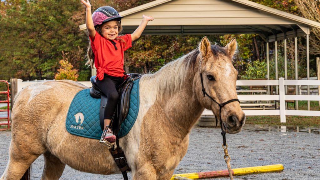 Little girl riding pony at HALTER's Therapeutic Horseback Riding program