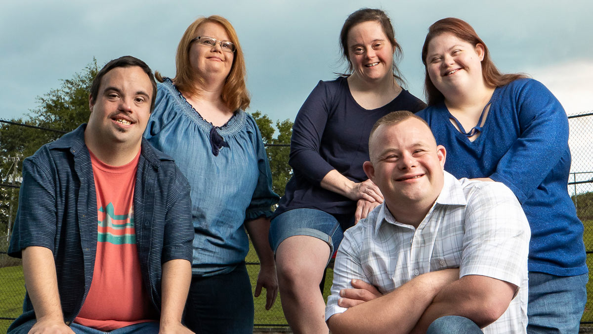 Five smiling faces - living with Down Syndrome.